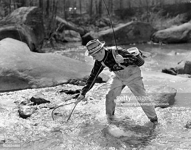 1930s 1940s MAN FLY FISHING WEARING WADERS HOLDING ROD AND NETTING A SUCCESSFUL CATCH
