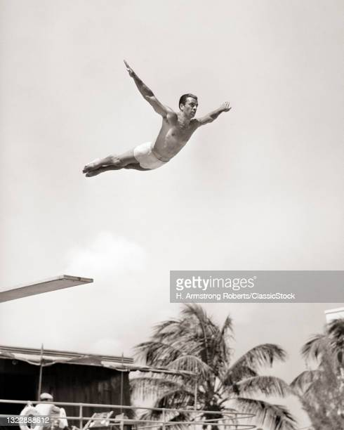 1930s 1940s Man High Diver Jumping Off Resort Swimming Pool Diving Board Perfect Form Caught In Mid-Air Miami Beach Florida USA.