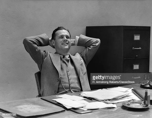 1930s 1940s MAN BUSINESSMAN RELAXING STRETCHING AT DESK IN OFFICE