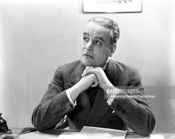 1930s 1940s MAN PORTRAIT AT DESK BUSINESSMAN WEARING SUIT HANDS CLASPED UNDER CHIN LOOKING OFF TO SIDE
