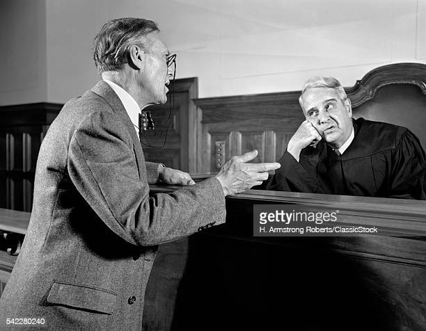 1930s 1940s MAN TRIAL LAWYER AT BENCH PLEADS POINT TO IMPATIENT BORED TIRED SKEPTICAL LEGAL COURT JUDGE