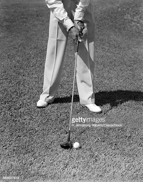 1930s 1940s MAN WAIST DOWN WITH GOLF CLUB ADDRESSING BALL