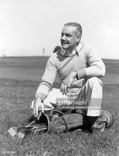 1930s 1940s MIDDLE AGE MAN KNEELING ON GRASS WITH HAND RESTING ON GOLF BAG AND CLUBS