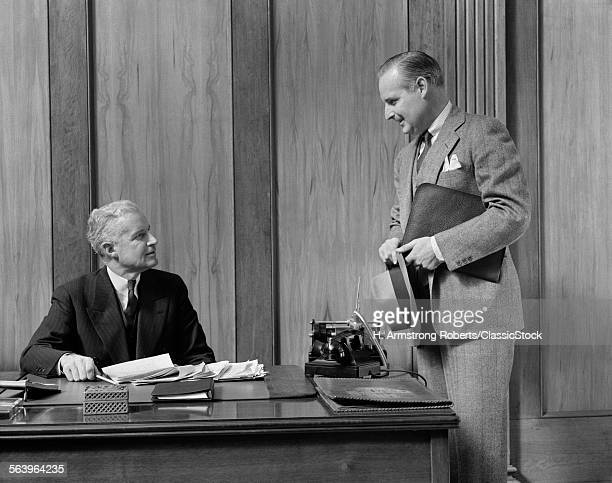 1930s 1940s MIDDLE AGE SALESMAN HAT AND BRIEFCASE IN HAND APPROACHING SPEAKING TO SENIOR BUSINESSMAN SITTING BEHIND OFFICE DESK