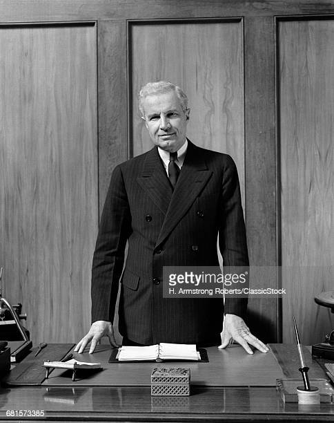 1930s 1940s MIDDLE AGED BUSINESS MAN STANDING BEHIND HIS DESK LOOKING AT THE CAMERA