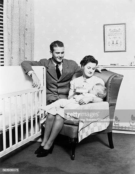 1930s 1940s MOTHER SITTING IN CHAIR IN NURSERY BABY 11 MONTHS ON LAP DRINKING FROM BOTTLE FATHER LOOKING ON LEANING ON CRIB