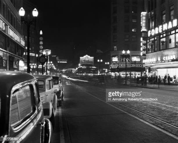 1930s 1940s NIGHT NEON SIGNS AND PARKED CARS ALONG 4TH AVENUE SEATTLE WASHINGTON USA