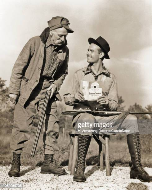 1930s 1940s OLD HUNTER HOLDING SHOTGUN SPEAKING TO SMILING YOUNGER MAN READING STRAIGHT SHOOTING INSTRUCTIONS HOLDING 22 RIFLE
