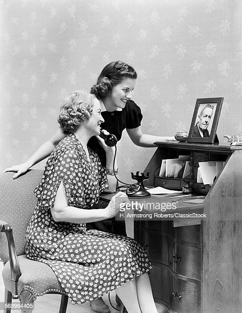 1930s 1940s OLDER MOTHER & DAUGHTER TALKING ON TELEPHONE TOGETHER LOOKING AT PICTURE OF ABSENT FATHER