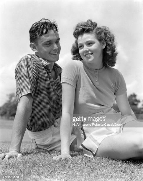 1930s 1940s PORTRAIT SMILING TEENAGE COUPLE BOY GIRL SITTING IN GRASS