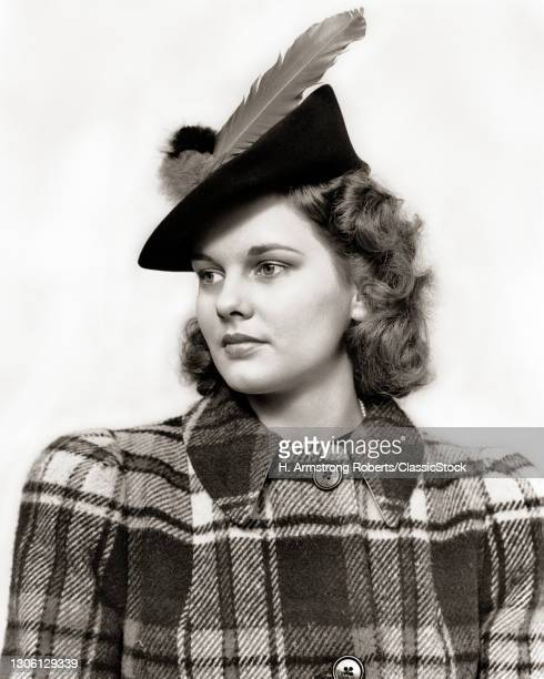 1930s 1940s Portrait Young Woman Teen Wearing Woolen Plaid Coat And Jaunty Hat With Large Feather Looking Off To The side.