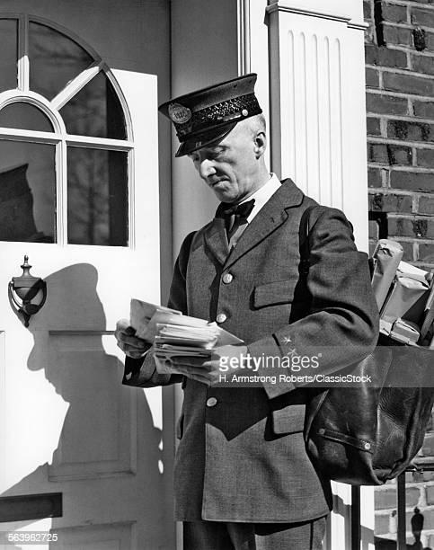 1930s 1940s POSTAL SERVICE UNIFORMED MAILMAN DELIVERING MAIL STANDING ON DOORSTEP SORTING LETTERS