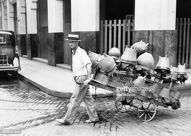 1930s 1940s POT SALESMAN LOOKING AT CAMERA PULLING HIS CART FULL OF CLAY POTS ON STREET HAVANA CUBA