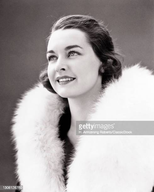 1930s 1940s Pretty smiling Brunette Woman Wearing Coat With White Fur Collar Looking Upwards.