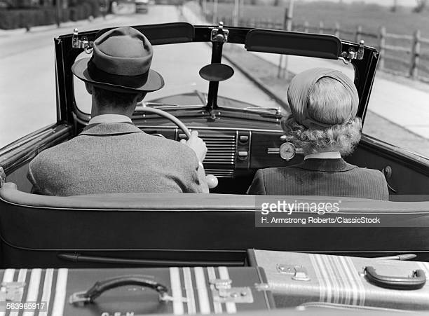 1930s 1940s REAR VIEW COUPLE DRIVING TOGETHER IN CONVERTIBLE LUGGAGE IN BACK SEAT
