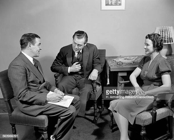 1930s 1940s SALESMAN TALKING TO COUPLE MAN AND WOMAN IN LIVING ROOM SALES PRESENTATION