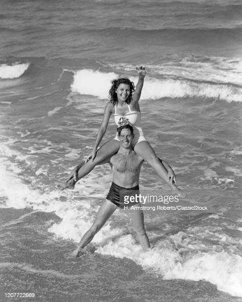 1930s 1940s smiling couple wearing bathing suits playing in surf ocean beach woman waving sitting on man shoulders Florida USA