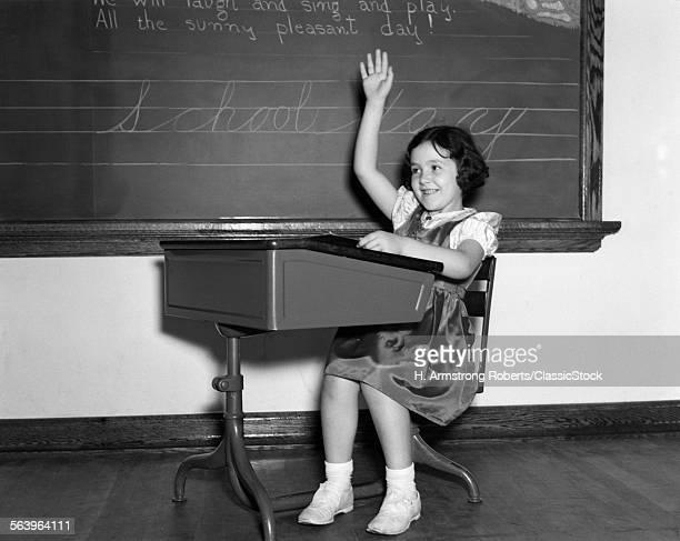 1930s 1940s SMILING GIRL SITTING AT DESK RAISING HER HAND