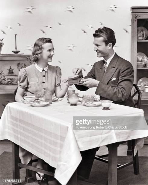 1930s 1940s SMILING MAN AND WOMAN AT BREAKFAST TABLE WOMAN SERVING TOAST MAN WEARING SUIT AND TIE