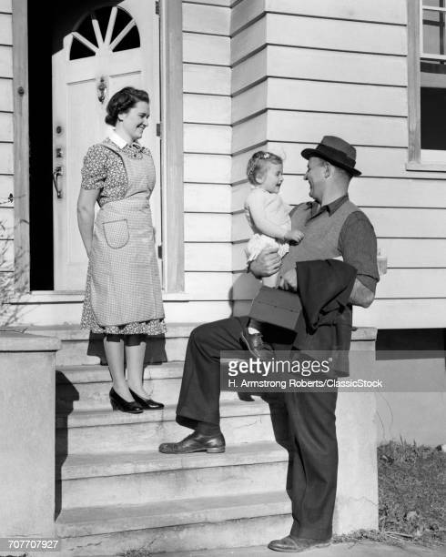 1930s 1940s SMILING MOTHER WATCHING HAPPY WORKING FATHER AT HOUSE FRONT STEPS HOLDING BABY DAUGHTER