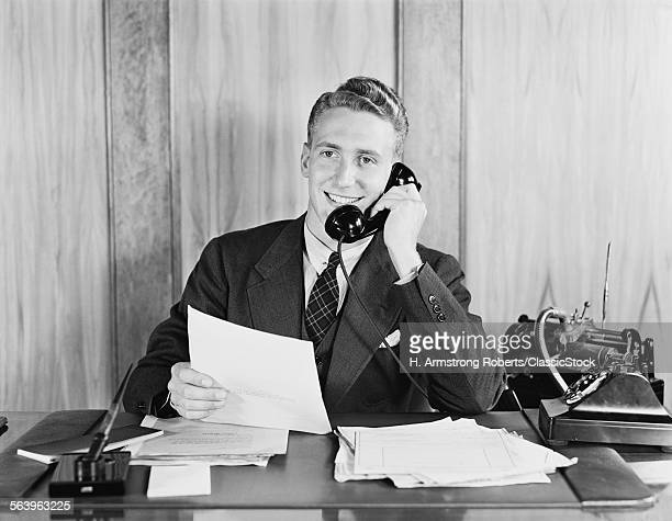 1930s 1940s SMILING BUSINESSMAN TALKING ON TELEPHONE SITTING AT DESK WITH DICTATION MACHINE