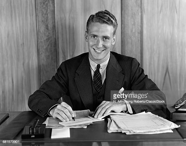 1930s 1940s SMILING BUSINESS MAN ABOUT TO SIGN A CHECK PEN IN HAND LOOKING AT CAMERA