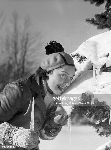 1930s 1940s SMILING SILLY WOMAN LICKING SNOW OFF OF PINE TREE BRANCH WEARING HAT WITH POM POM TASSEL LOOKING AT CAMERA
