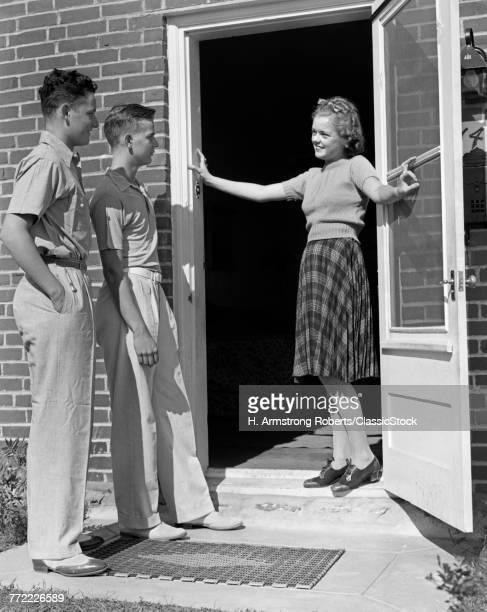 1930s 1940s TEEN GIRL SMILING WELCOMING TWO BOYS AT FRONT DOOR