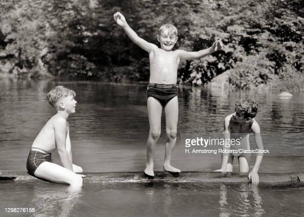 1930s 1940s Three Boys Friends Brothers Playing Together Balancing On Floating Log In Rural Swimming Hole Wearing Bathing Suits.