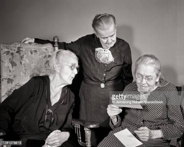 1930s 1940s Three Elderly Senior Gray Hair Women Reading Over Shoulder Received Mail Letter Check In Old Age Retirement Home