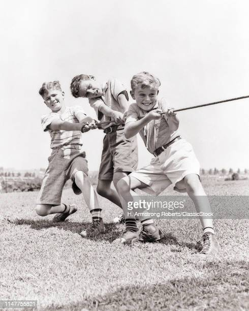 1930s 1940s THREE SMILING ENERGETIC TEEN BOYS STRUGGLING TOGETHER PULLING ROPE IN TUG OF WAR WEARING SUMMER SHORTS AND SNEAKERS
