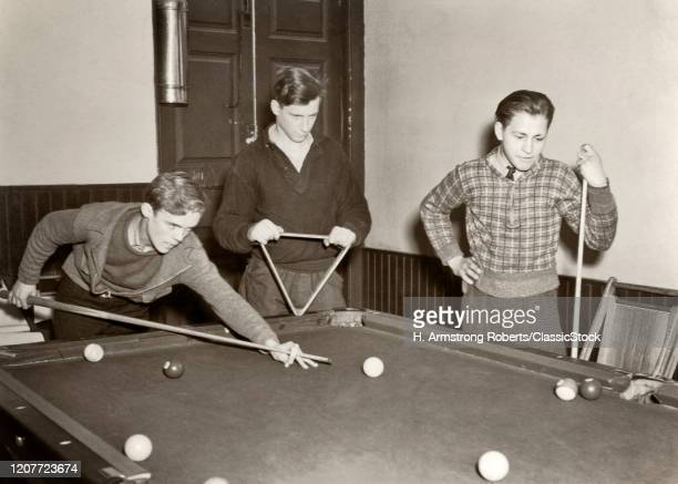 1930s 1940s three teen boys shooting pool in a neighborhood recreational center.
