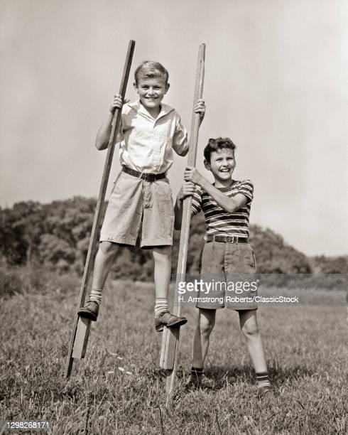 1930s 1940s Two Boys Wearing Shorts Playing Together Outdoors One Walking On Stilts Looking At Camera The Other Helping Balance.