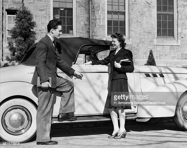 1930s 1940s TWO COLLEGE STUDENTS HOLDING BOOKS STANDING BY CONVERTIBLE TOP CAR