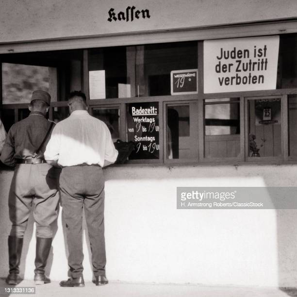 1930s 1940s Two Men One In Nazi Uniform Jack Boots At Coffee Shop; Sign In Window Says Admission Of Jews Is Forbidden.