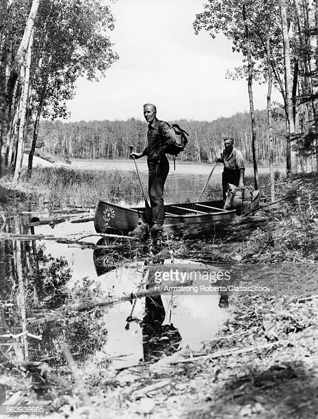 1930s 1940s TWO MEN STANDING IN CANOE IN SHALLOW WATER OF LAKE HOLDING OARS WEAR BACKPACKS LAKE OF THE WOODS ONTARIO CANADA