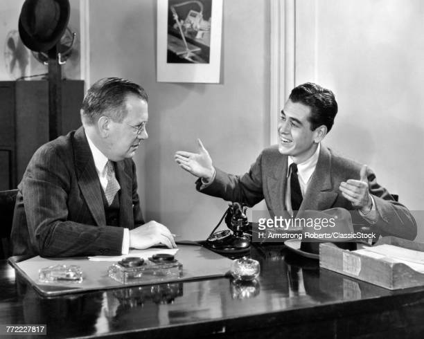 1930s 1940s TWO MEN SEATED AT DESK YOUNGER MAN TALKING GESTURING ARMS UP OLDER MAN LISTENS