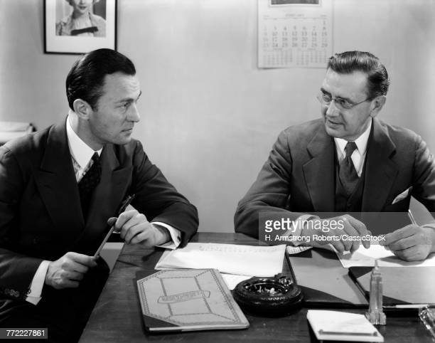 1930s 1940s TWO BUSINESSMEN IN OFFICE SITTING AT DESK TALKING