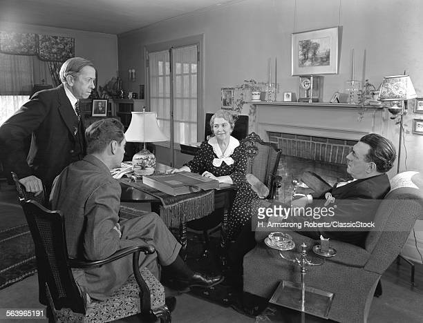 1930s 1940s TWO SALESMEN MAKING SALES PRESENTATION TO OLDER COUPLE HUSBAND AND WIFE SITTING IN LIVING ROOM