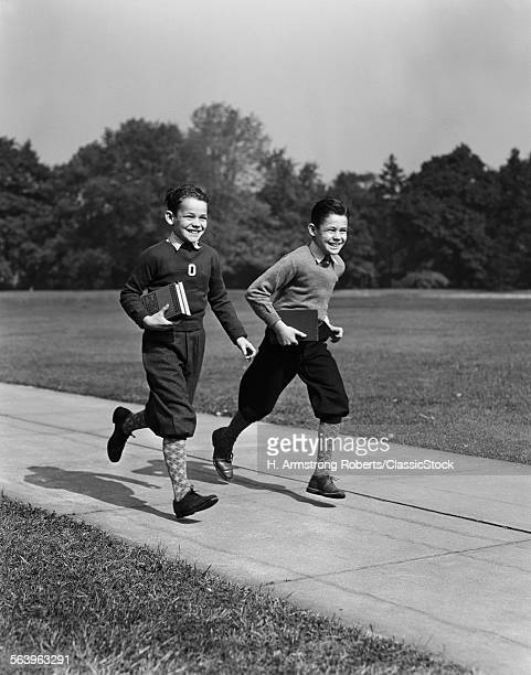 1930s 1940s TWO SMILING BOYS RUNNING CARRYING SCHOOL BOOKS