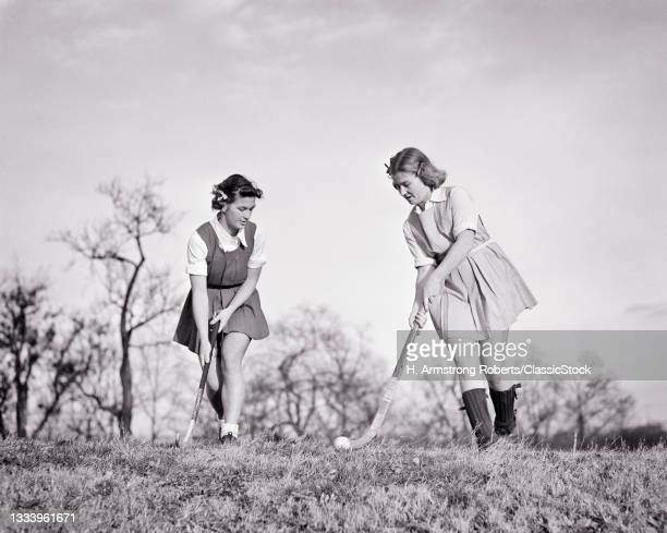 1930s 1940s Two Teenage Athletic Girls High School Students Playing Field Hockey Outdoors .