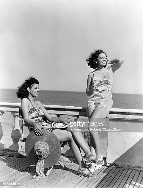 1930s 1940s TWO WOMEN SITTING ON HOTEL DECK BEACH SIDE IN ONE PIECE BATHING SUIT FASHION FLORIDA USA