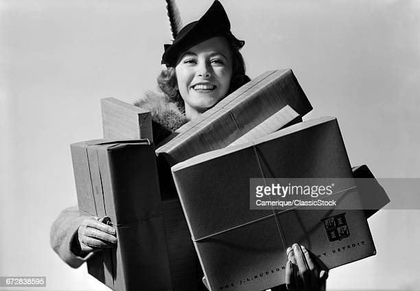 1930s 1940s WOMAN SHOPPING CARRYING LOTS OF PACKAGES LOOKING AT CAMERA