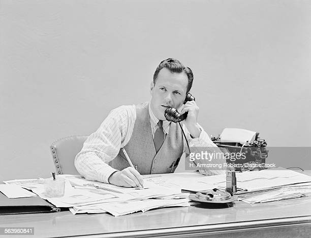 1930s 1940s YOUNG BUSINESSMAN SITTING AT DESK TALKING ON TELEPHONE TYPEWRITER WEARING VEST HOLDING PENCIL SHIRTSLEEVES