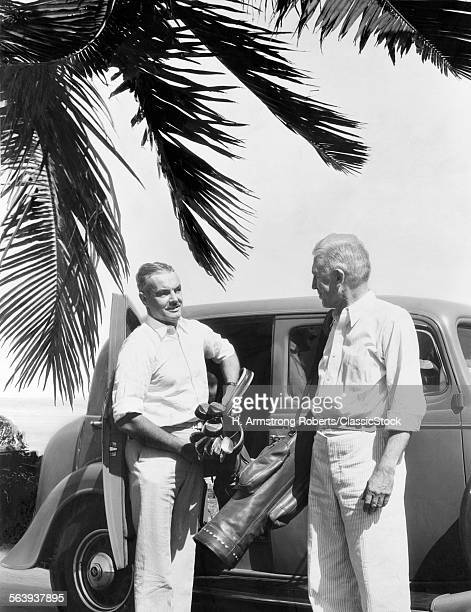 1930s 2 ELDERLY MEN STANDING BY CAR CARRYING GOLF BAG PALM TREE FROND IN CORNER