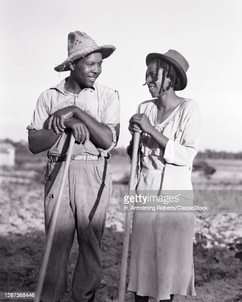 1930s African-American Husband Wife Looking At Each Other Smiling Hoeing Tobacco Leaning On Tools Together North Carolina USA