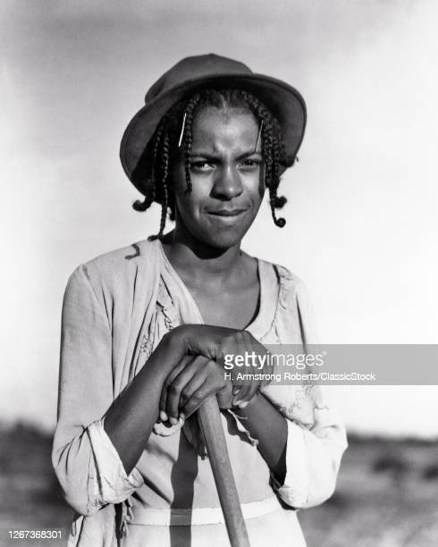 1930s African-American Woman Looking At Camera Leaning On Handle Of A Hoe Working Tobacco North Carolina USA