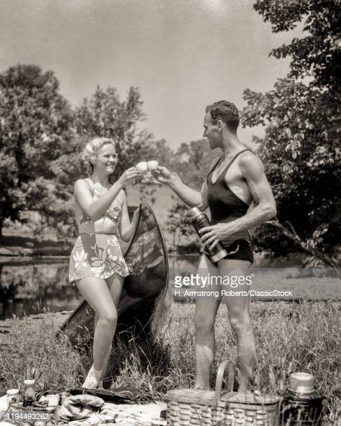 1930s ATHLETIC HEALTHY COUPLE MAN WOMAN WEARING BATHING SUITS TOASTING ONE ANOTHER WHILE ENJOYING OUTDOOR PICNIC BY RURAL LAKE
