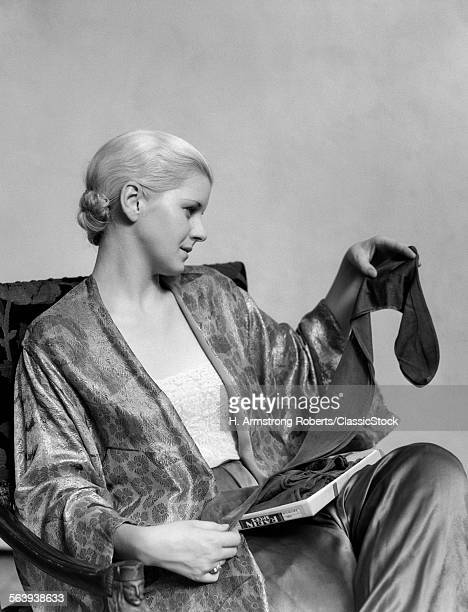 1930s BLOND WOMAN WEARING SILK PAJAMAS TAKING A PAIR OF SHEER STOCKINGS FROM BOX