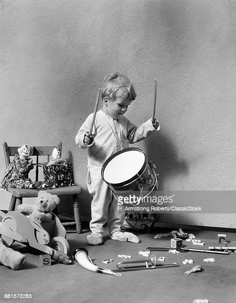 1930s BOY IN PAJAMAS BEATING ON TOY DRUM SURROUNDED BY TOYS ON CHAIR AND FLOOR